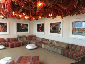 Sitting area in the museum with a  beautiful piece of art on the ceiling called Web_Orange #5 by Jennifer Jenkins